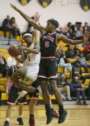 Greece Athena's DeAndre Newsome, left, runs out of room as he tries to drive to the basket as Hilton's Najier Daniels defends the paint during their game at Greece Athena High School Monday, Jan. 28.
