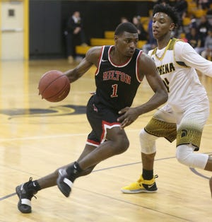 Hilton's TahJae Hill, left, drives to the basket as Athena's Melvin Council, Jr., right, defends.