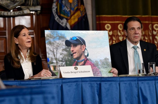 Linda Beigel Schulman, left, holds a photograph of her son Scott Beigel, who was killed by gun violence while speaking with New York Gov. Andrew Cuomo and gun safety advocates in the Red Room during a news conference at the state Capitol on Tuesday, Jan. 29, 2019, in Albany, N.Y.