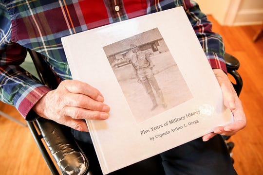 Art Gregg holds a book his daughter made for him at his home in Silverton on Friday, Jan. 25, 2019. The book consists of photos, short stories and a timeline of his military service years.