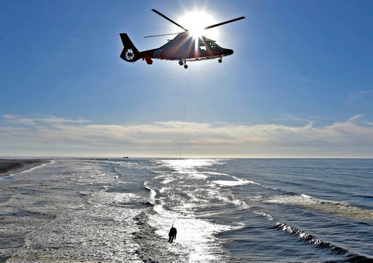 In this Nov. 7, 2018 file photo, Coast Guard personnel from Air Station Astoria in Oregon participate in a rescue exercise near Cape Disappointment, Wash. Anticipating possible additional federal government shutdowns, Oregon's Senate president has prepared a bill that will allow federal employees who are working but not being paid to receive unemployment benefits. The draft of the bill also would allow a state-funded program to pay unemployment benefits to active duty U.S. Coast Guard personnel stationed in Oregon who are legally compelled to provide regular service without compensation during a shutdown.