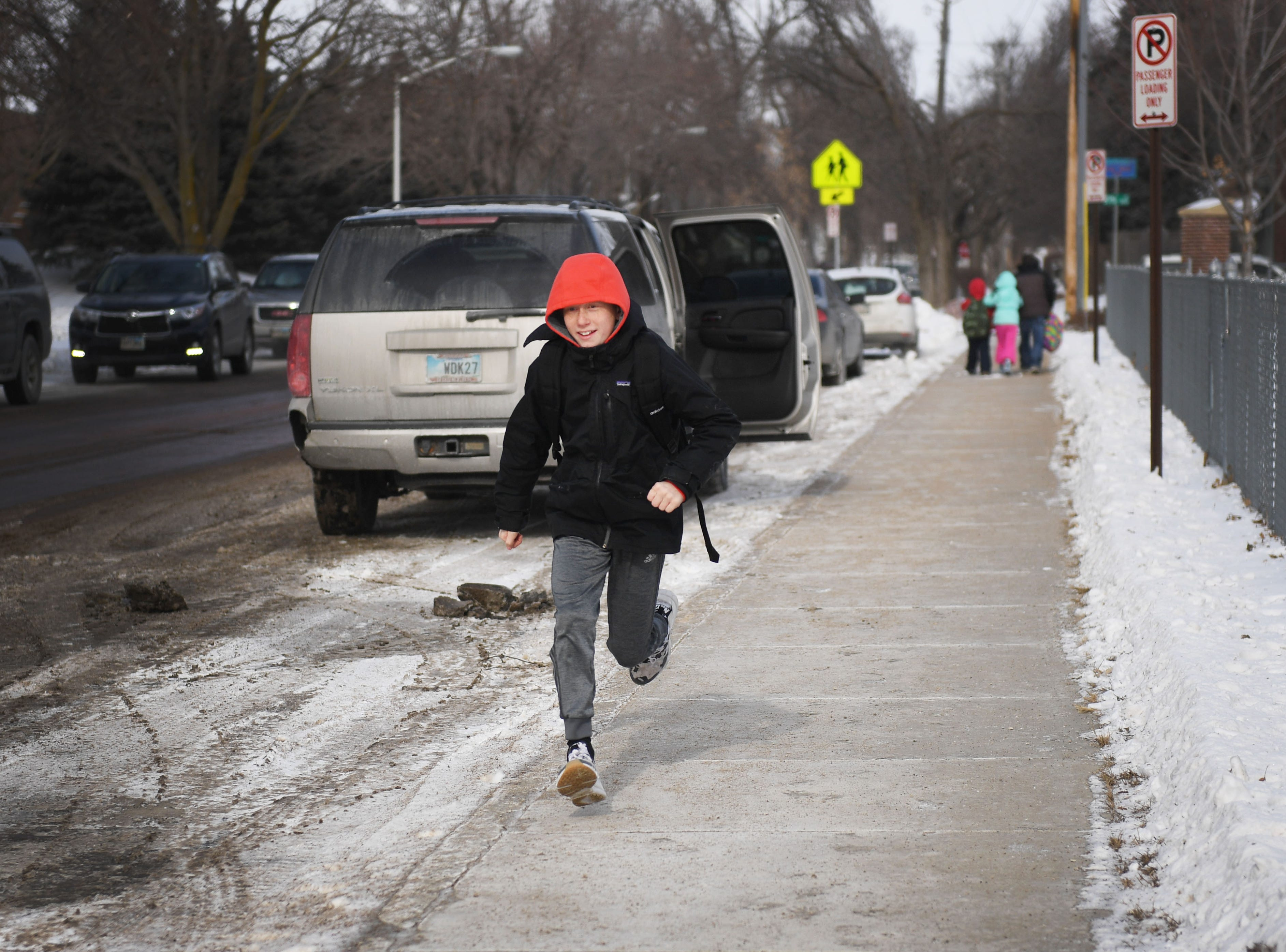 Carson Nickles runs down the sidewalk after early dismissal at Susan B. Anthony Elementary School, Tuesday, Jan. 29, in Sioux Falls. Area schools had early dismissal Tuesday because of severe weather.