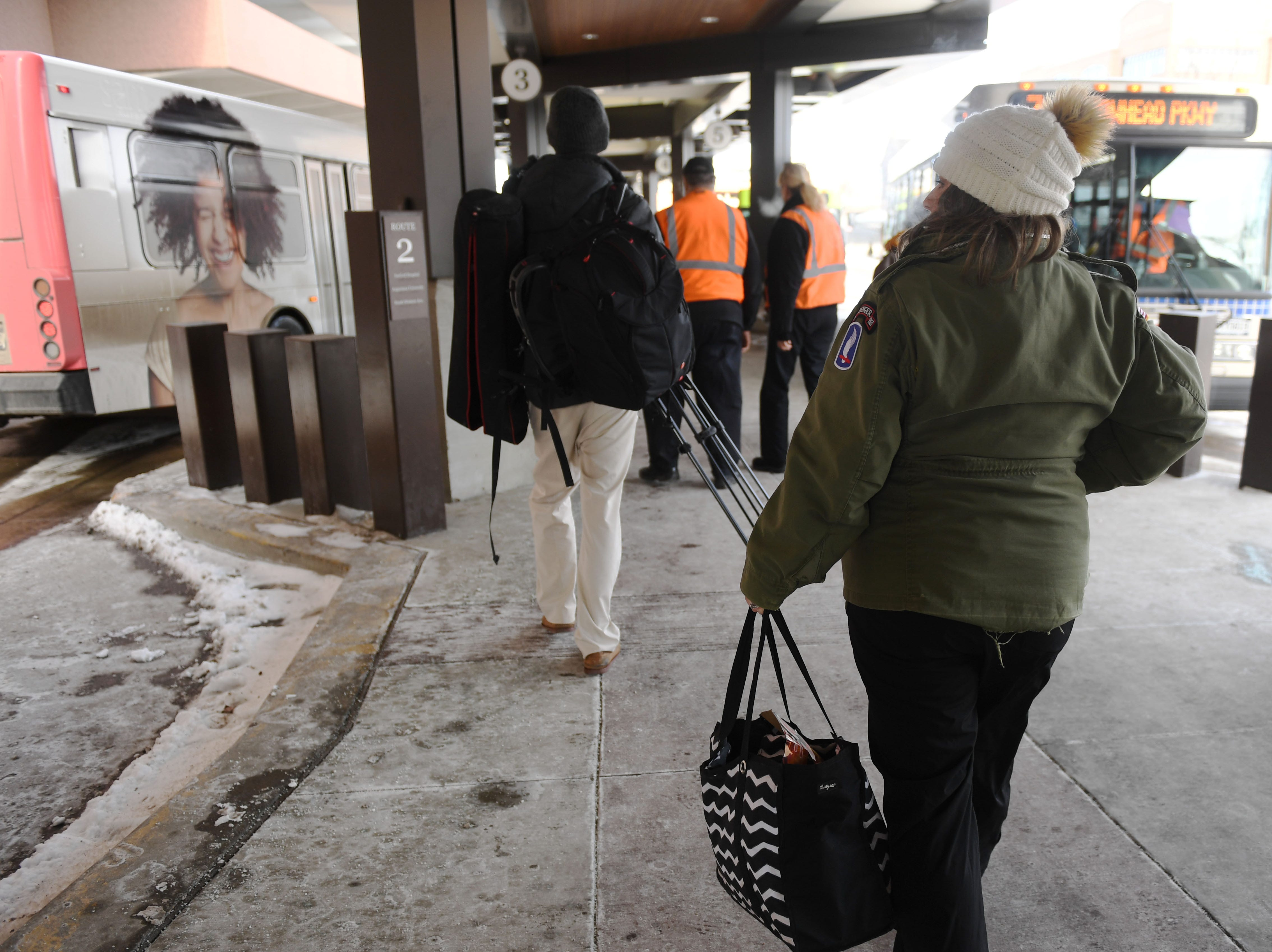 Amy Lawrence walks around the The Bus Stop downtown terminal handing out hand warmers to passengers, Tuesday, Jan. 29, in Sioux Falls.