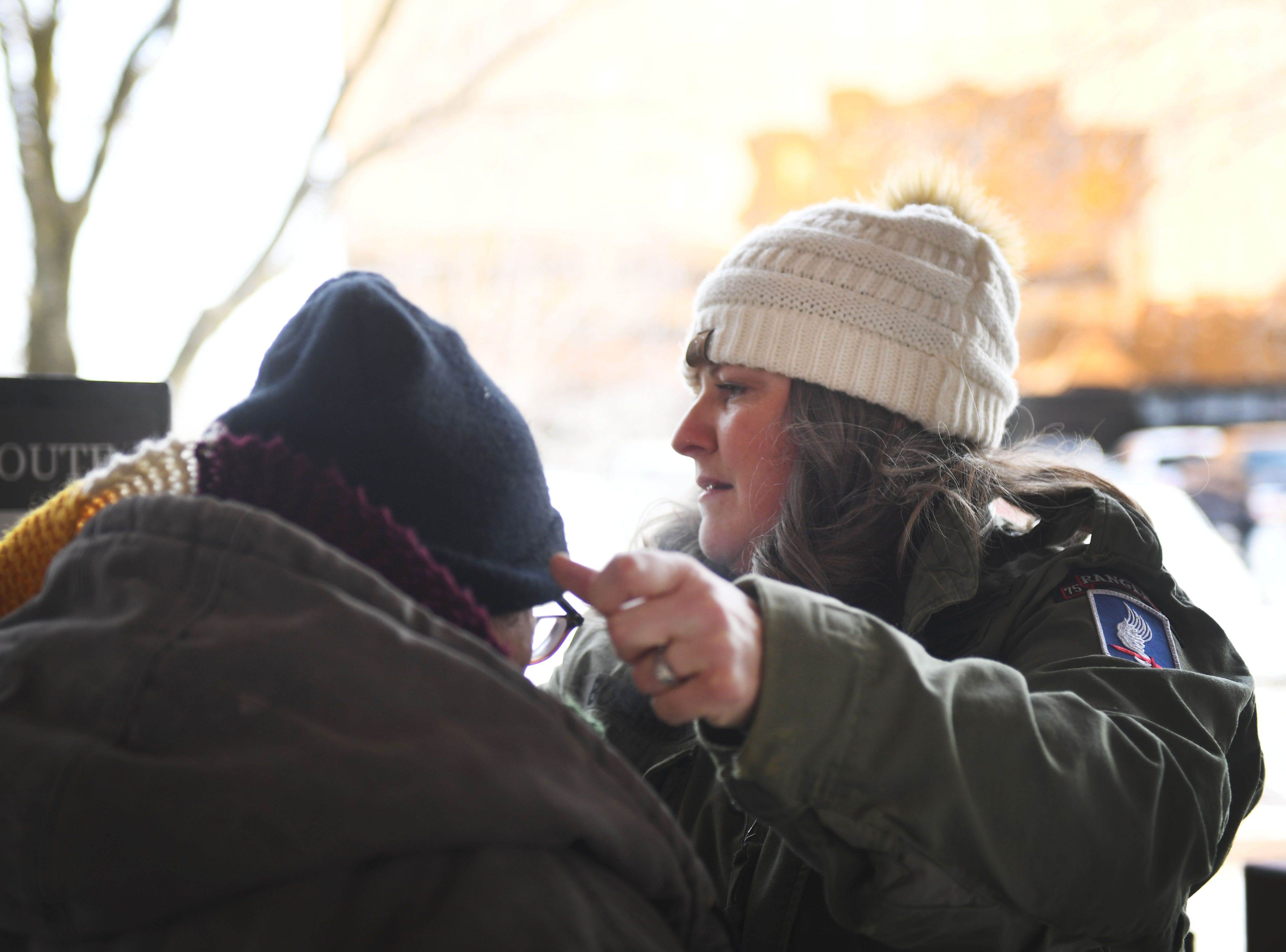 Amy Lawrence fixes a bus passengers hat and then hands them a hand warmer at the The Bus Stop downtown terminal, Tuesday, Jan. 29, in Sioux Falls.