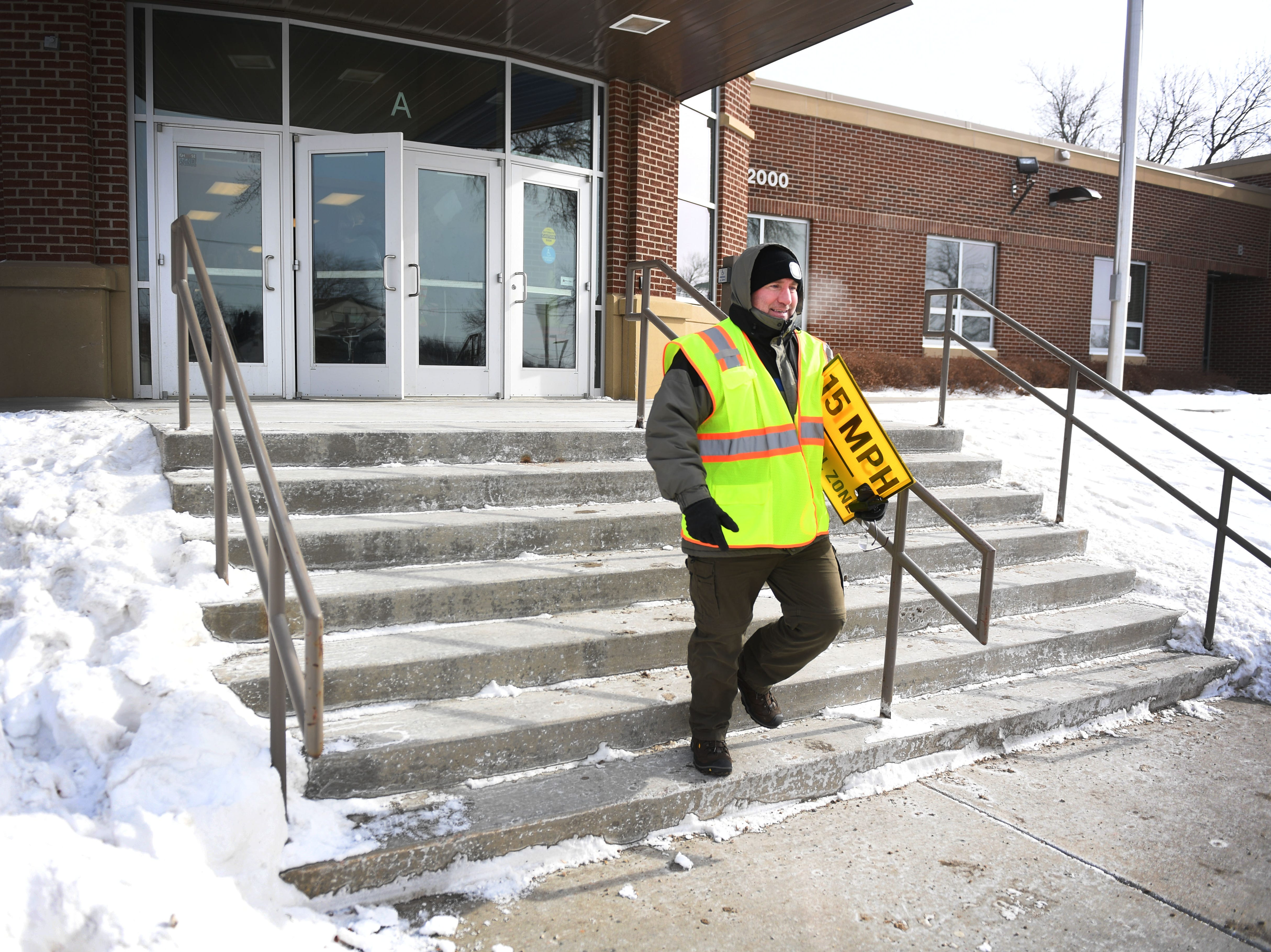 Terrin Haggerty, counselor at Susan B. Anthony Elementary School, is on crosswalk duty for early dismissal Tuesday, Jan. 29, in Sioux Falls. Area schools had early dismissal Tuesday because of severe weather.