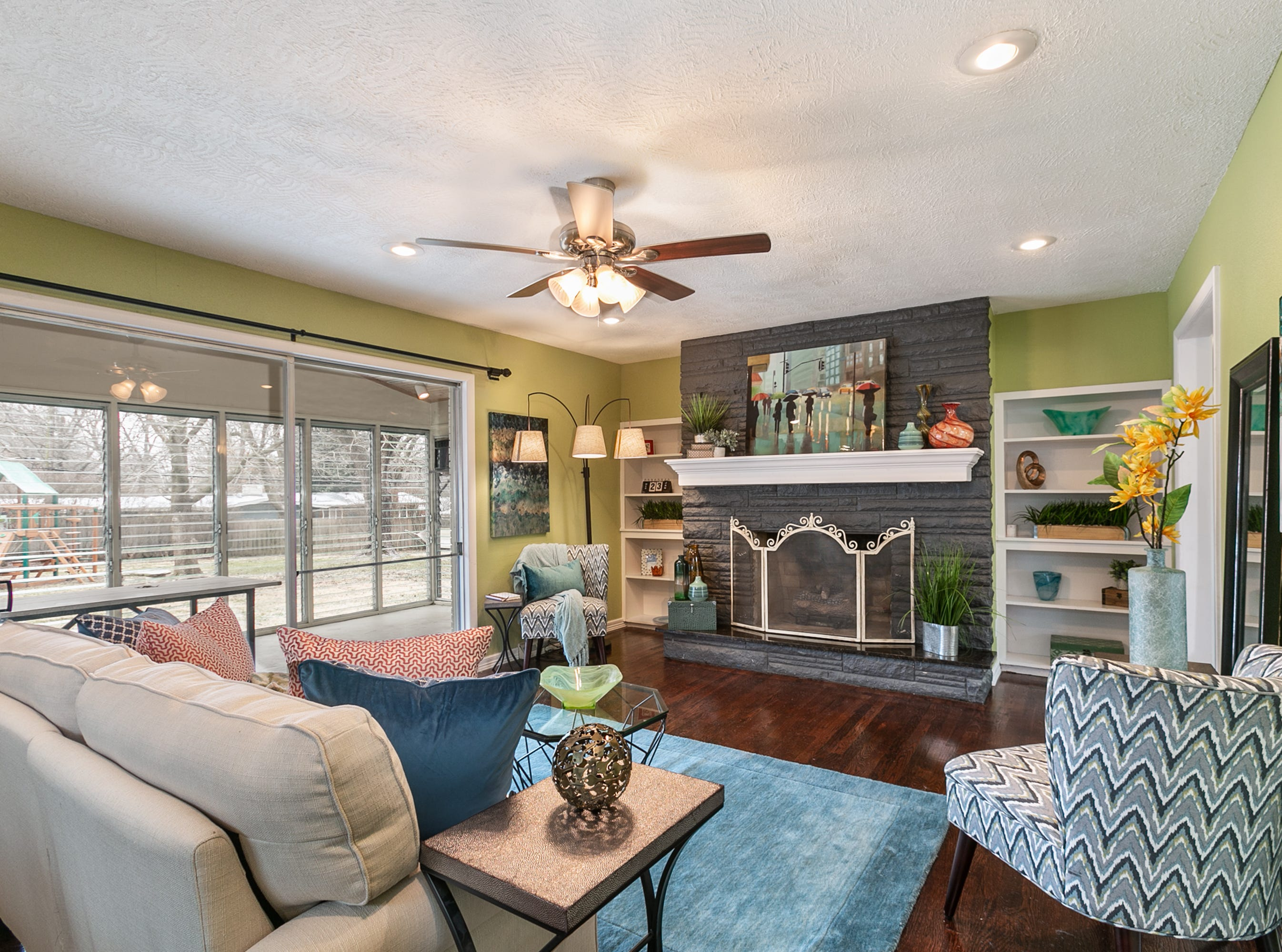 The den features a large brick fireplace and loads of sunlight, thanks to large sliding doors that open onto the sun porch. Tile was replaced with hardwoods, which were finished to tie in with the original hardwoods found elsewhere in the house.