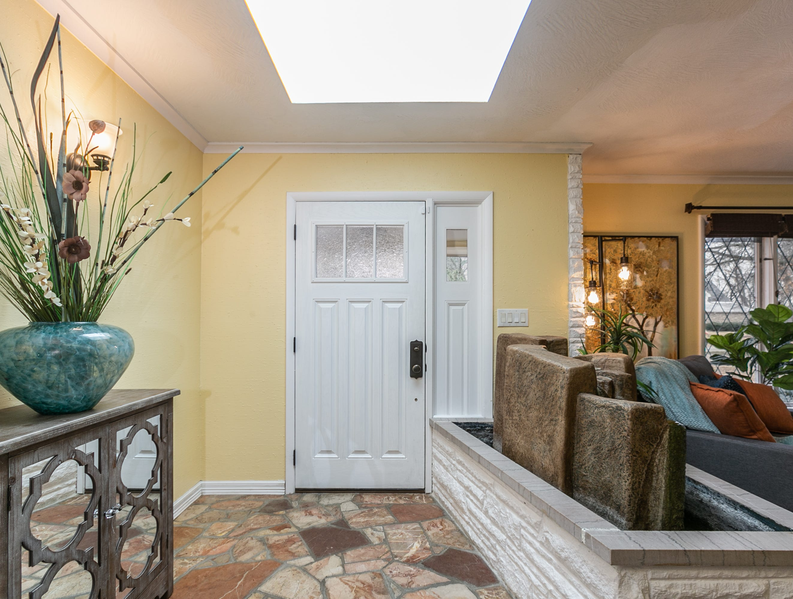 The entryway features the original marble flagstone floor and a planter that has been transformed into a water feature.