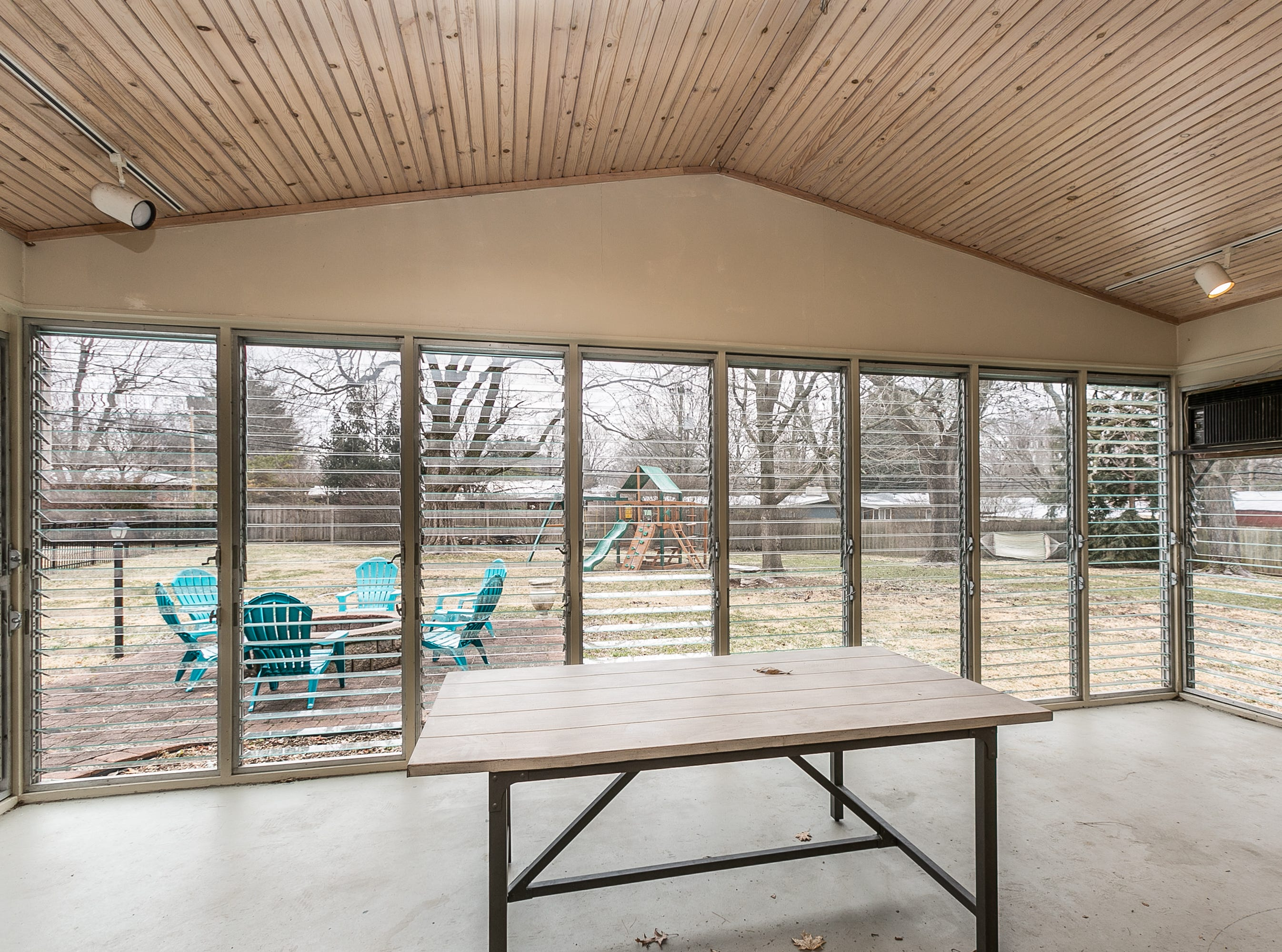 The sunroom features jalousie windows and an excellent view of the backyard and (left) the pool.