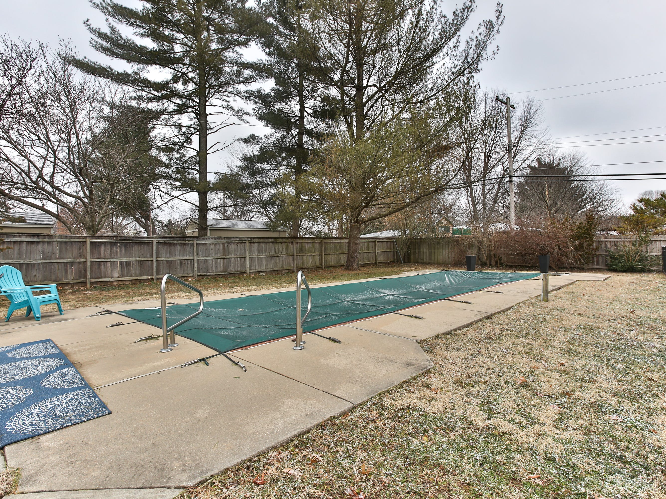 The in-ground pool, now closed for the season, is separated from the larger play area of the backyard by an attractive, yet effective, iron fence.