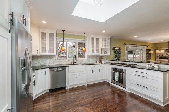 The remodeled kitchen features new everything, from floors to reeded-glass-front cabinets. The windows over the sink look out to the spacious backyard and in-ground pool.