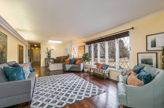 The large living room features Carthage stone accents that reflect the home's exterior and hardwood floors. The original diamond-grille windows allow ample light to flow in.