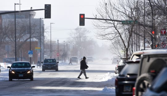 Wind-blown snow provides a chilly backdrop as people cross St. Germain Street as temperatures continue to drop Tuesday, Jan. 29, in St. Cloud.