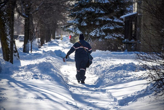 A postal worker delivers mail in sub-zero temperatures Tuesday, Jan. 29, in St. Cloud.