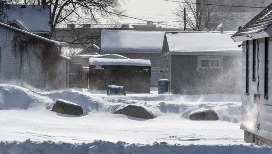 Wind blows snow through an alleyway as temperatures plummet Tuesday, Jan. 29, in St. Joseph.