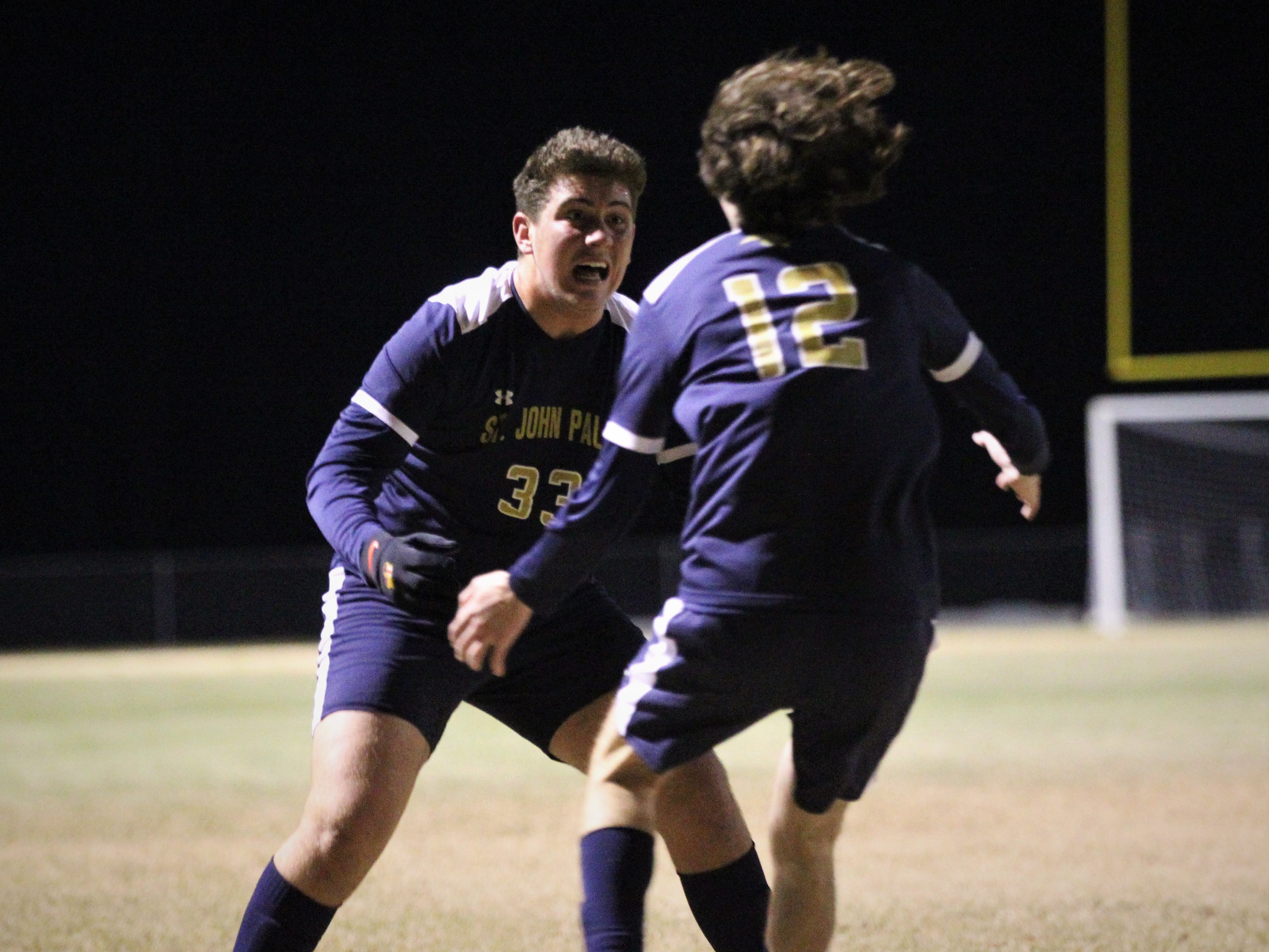 St. John Paul II midfielder Rocco Ricco (33) runs up to senior Tyler Lattner after Lattner headed in a goal off Ricco's throw-in as SJP2 beat Wakulla Christian 2-0 during a District 1-1A boys soccer district quarterfinal on Jan. 28, 2019.