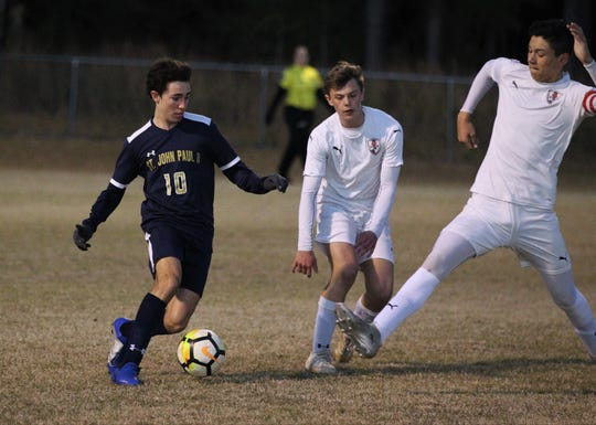 St. John Paul II's Spencer Duffey tries to dribble between two Wakulla Christian players as St. John Paul II beat Wakulla Christian 2-0 during a District 1-1A boys soccer district quarterfinal on Jan. 28, 2019.