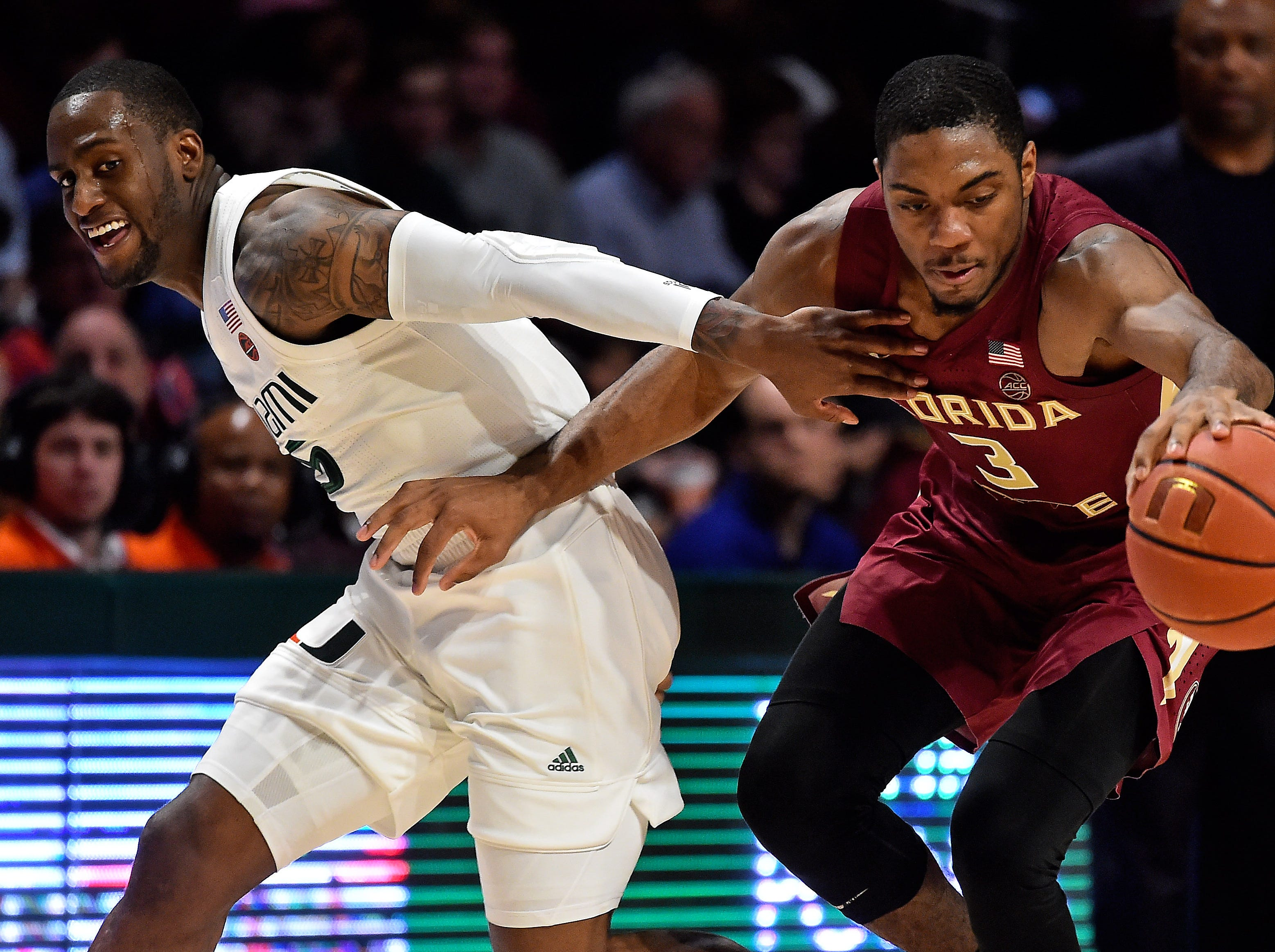Jan 27, 2019; Coral Gables, FL, USA; Miami Hurricanes guard Zach Johnson (5) and Florida State Seminoles guard Trent Forrest (3) chase a loose ball during the second half at Watsco Center. Mandatory Credit: Jasen Vinlove-USA TODAY Sports
