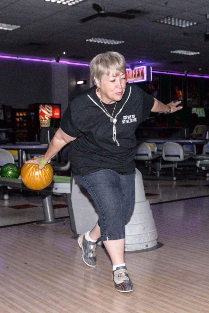 Tena Sigmon shows great form while bowling at the Cosmic Family Fun event  to support HANDSof St. Lucie County.