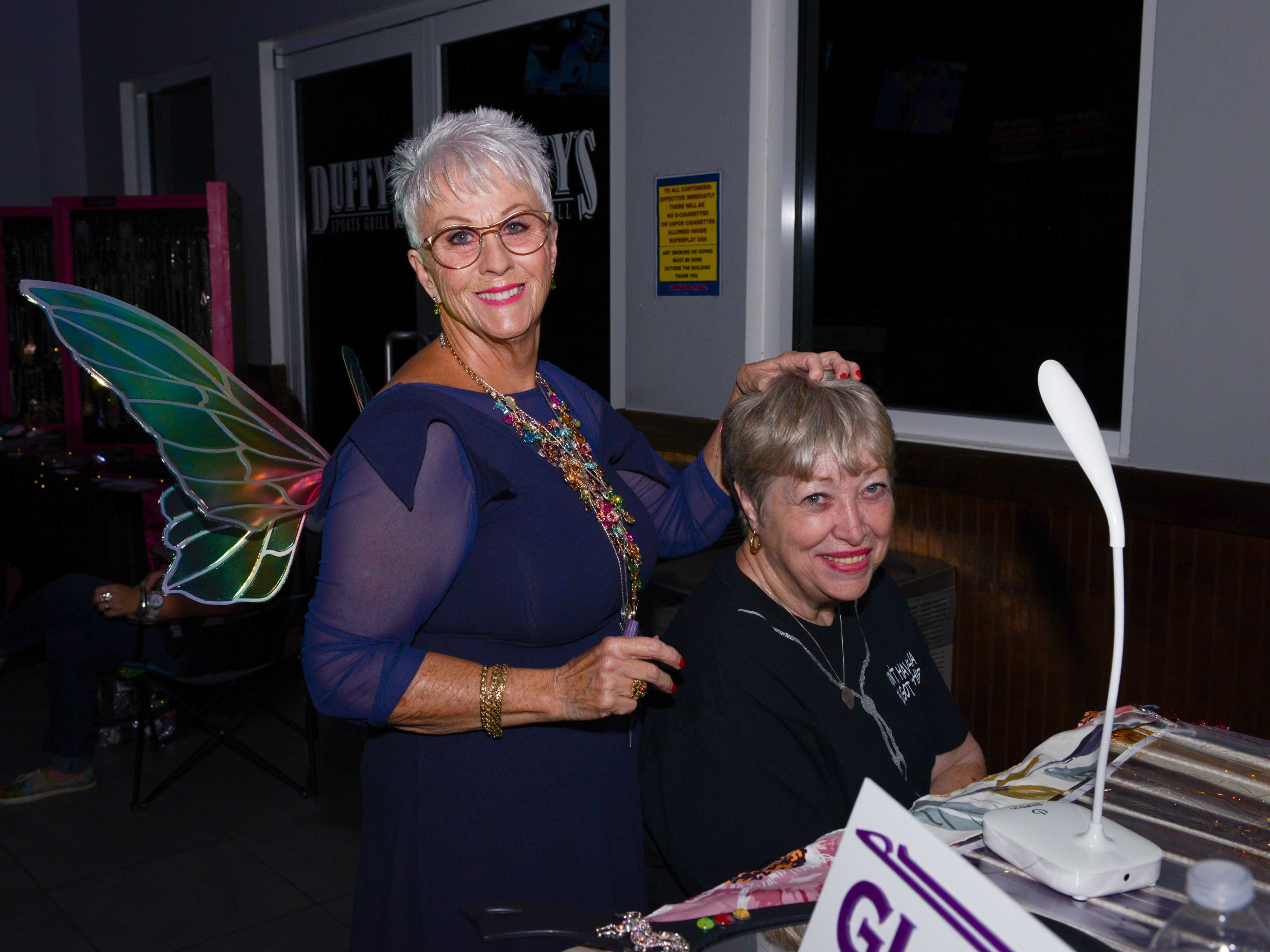 Susan Hutchinson gives Tena Sigmon fairy hair at the Cosmic Family Fun event  to support HANDSof St. Lucie County.