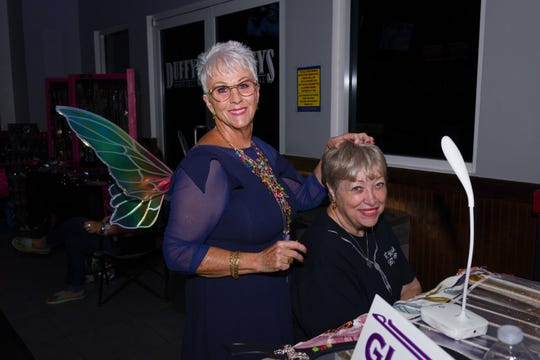 Susan Hutchinson gives Tena Sigmon fairy hair at the Cosmic Family Fun event  to support HANDS of St. Lucie County.