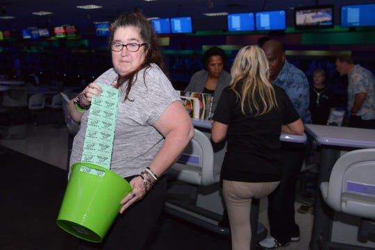 Susan Scherer sells raffle tickets at the Cosmic Family Fun event to support HANDSof St. Lucie County.