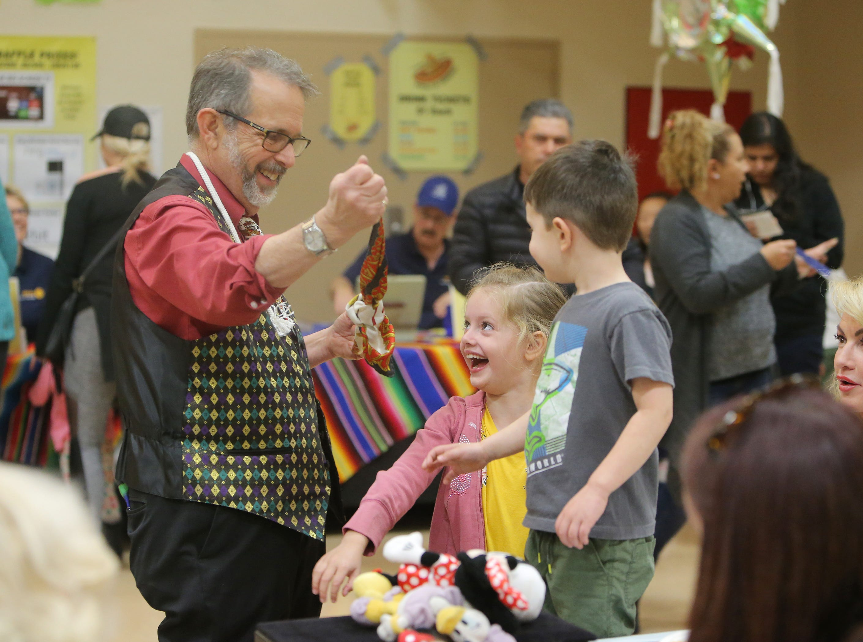 Rotary Club of Camarillo member and magician Paul Dwork performs a trick for Parker Jones and her brother Adam Jones during the annual Viva la Comida Dinner and Fiesta fundraiser on Monday at the Camarillo Community Center. Dwork has been doing magic for the event for 23 years.
