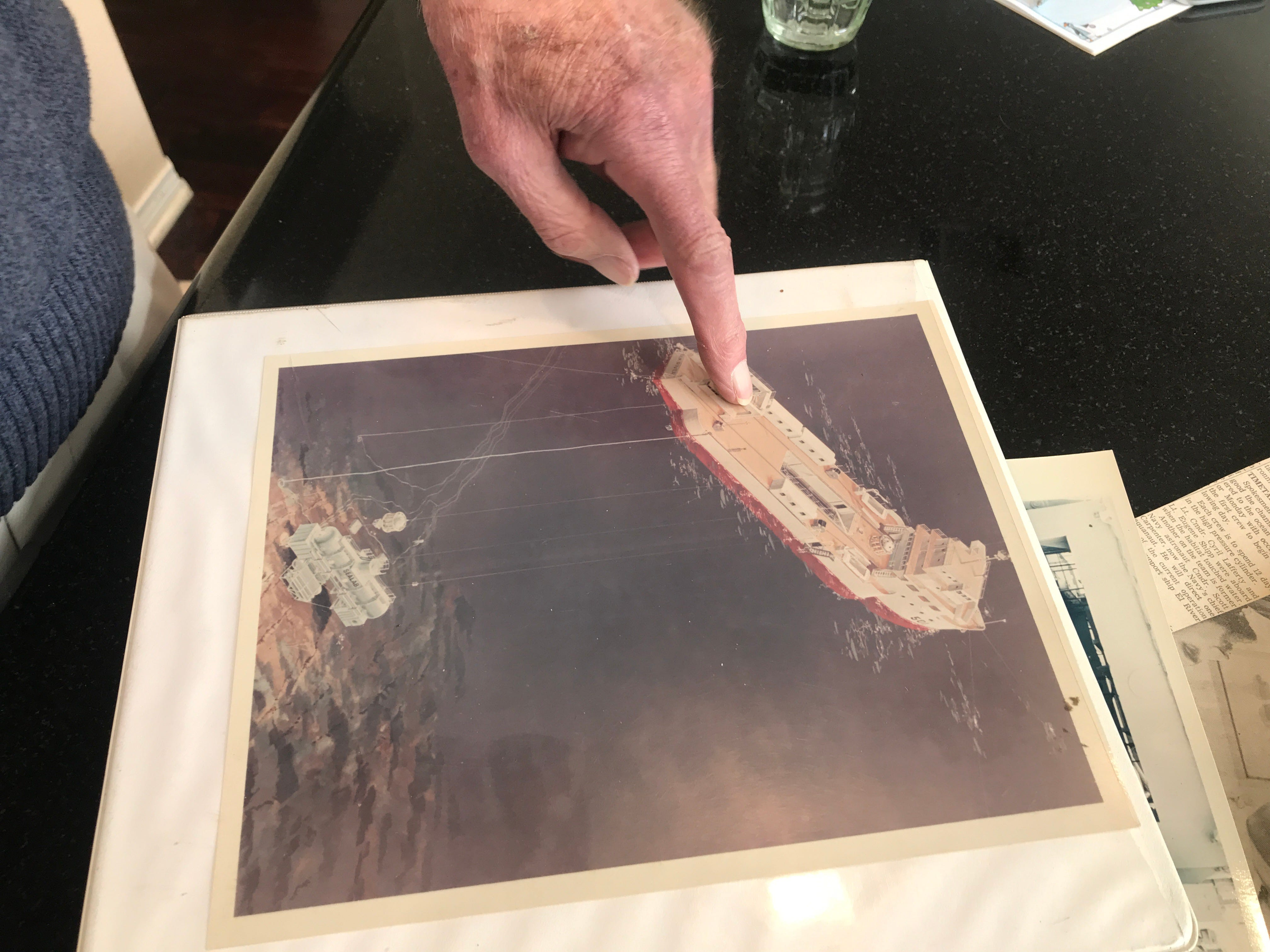 Bob Bornholdt points to an illustration of the ship and underwater Sealab laboratory that were used by the navy's pioneering aquanauts.