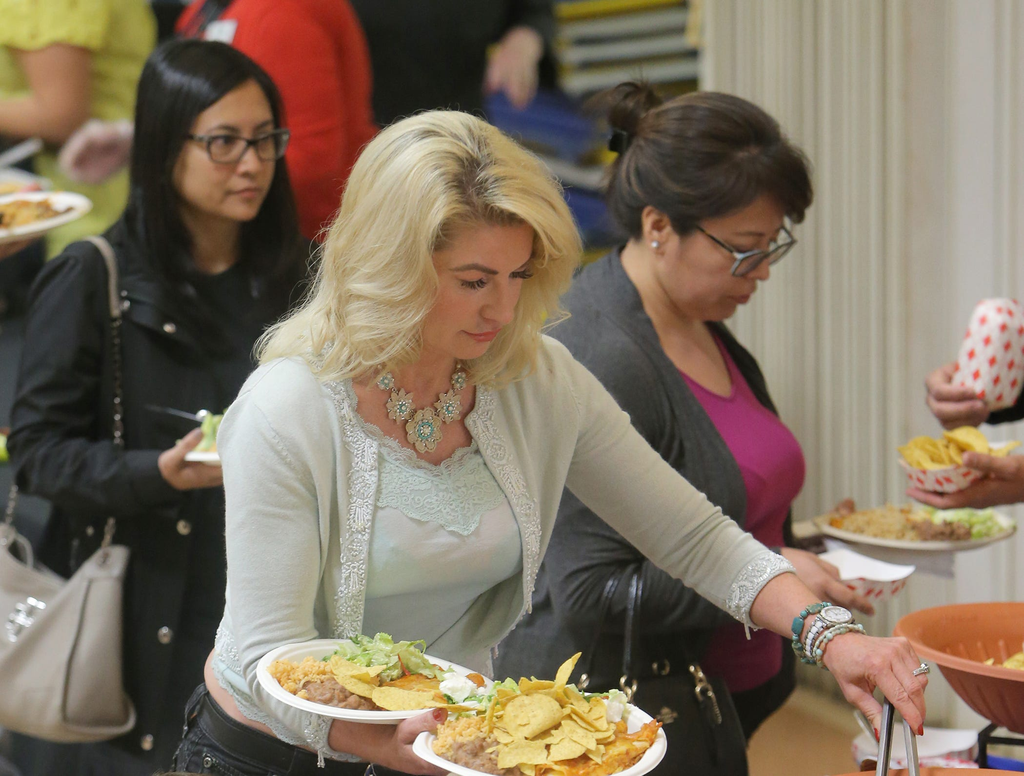 Adam Jones watches as his grand-aunt Christine Popok, a Rotary Club of Camarillo member, adds chips to their enchiladas dinner during the annual Viva la Comida Dinner and Fiesta fundraiser on Monday at the Camarillo Community Center.