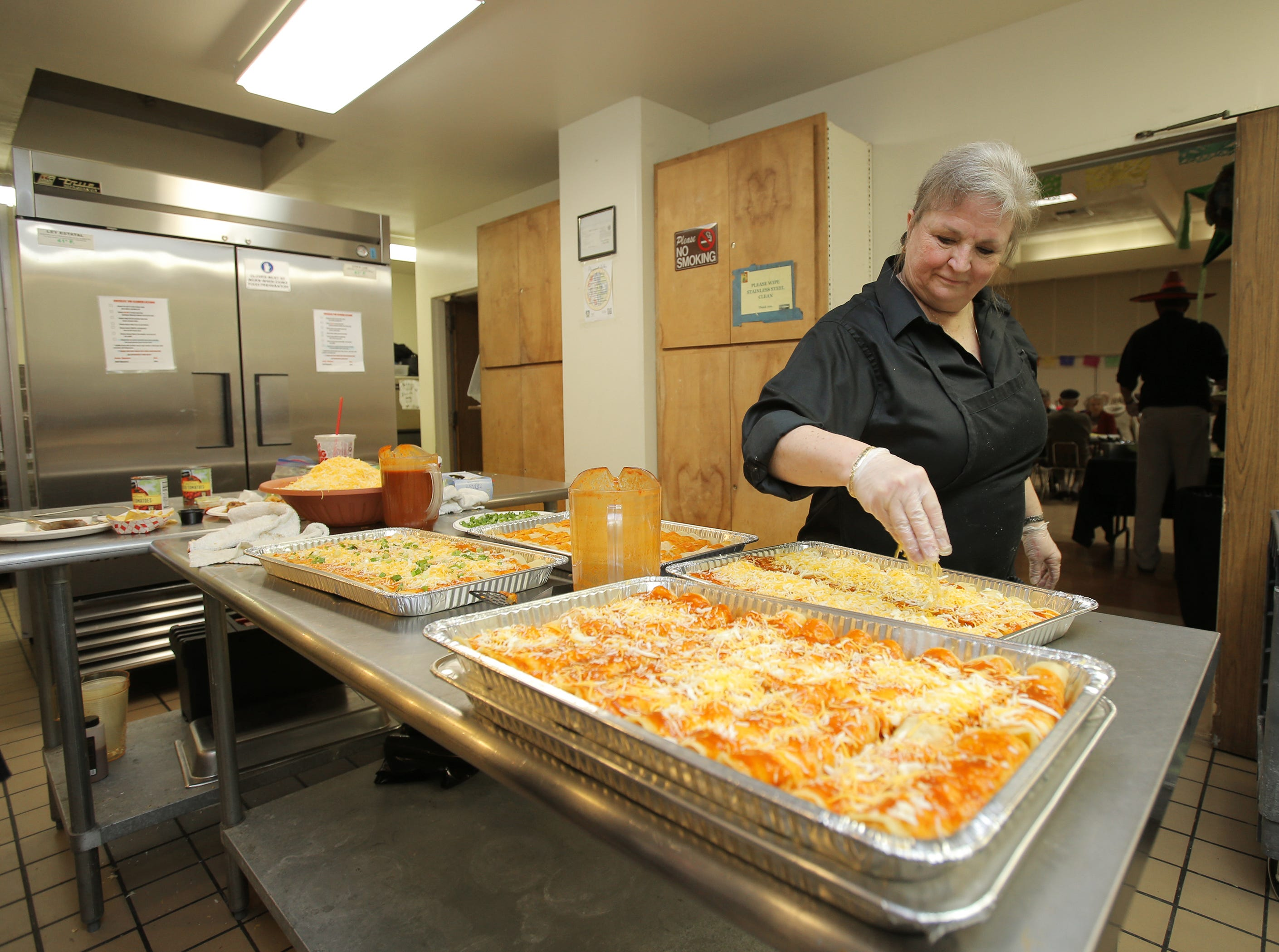 J Funk, of May's Kitchen, adds the final layer of cheese to a tray of enchiladas during the annual Viva la Comida Dinner and Fiesta fundraiser hosted by the Rotary Club of Camarillo on Monday at the Camarillo Community Center. All of the money raised goes toward scholarships and local charities, included the Boys & Girls Club.
