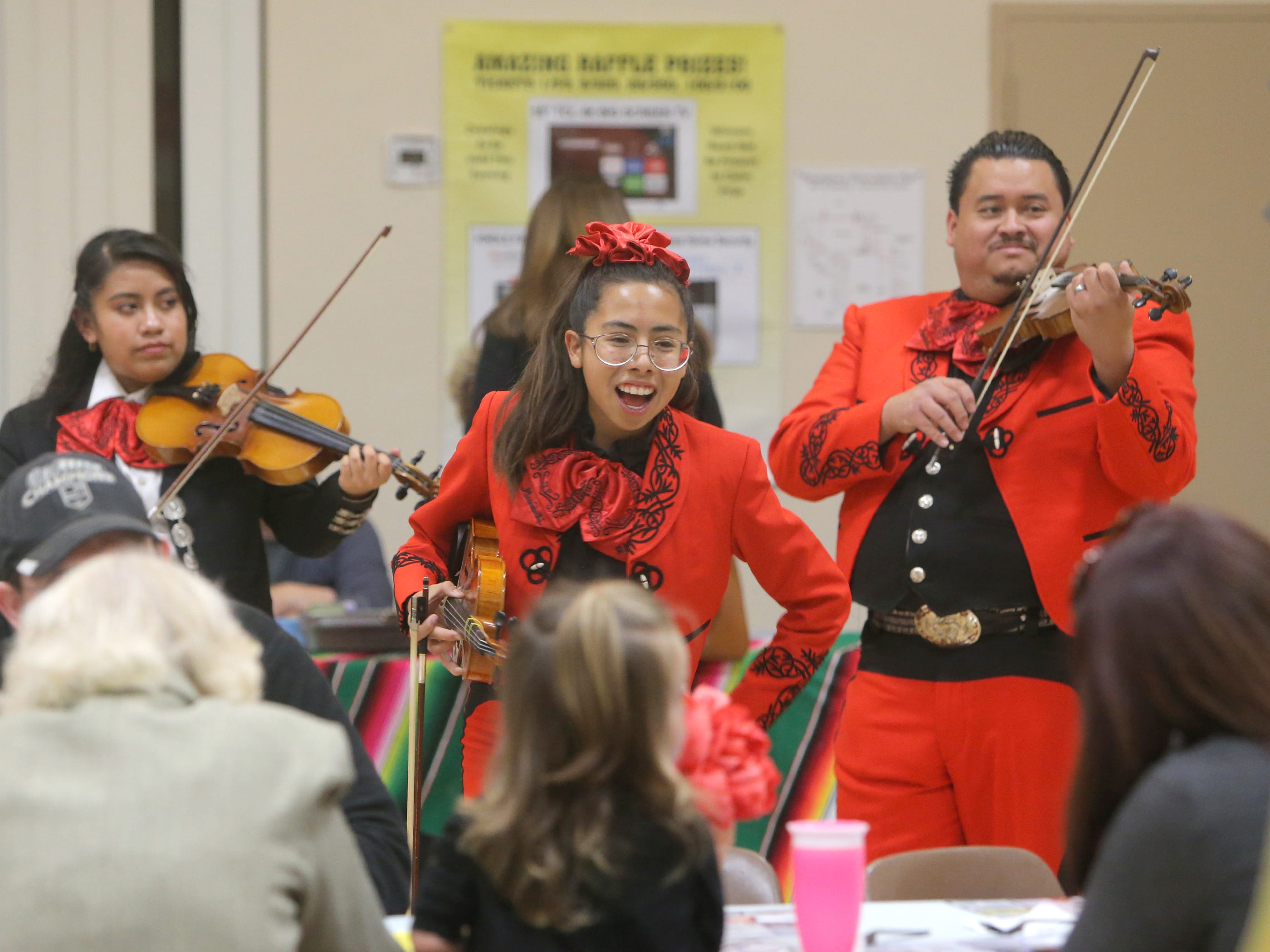 Rio Mesa High School's Brisa Garcia, center, entertains guests with her teacher Dominic Rivera, right, and some of her schoolmates during the annual Viva la Comida fundraiser Monday at the Camarillo Community Center. Garcia is a member of the school's mariachi class.