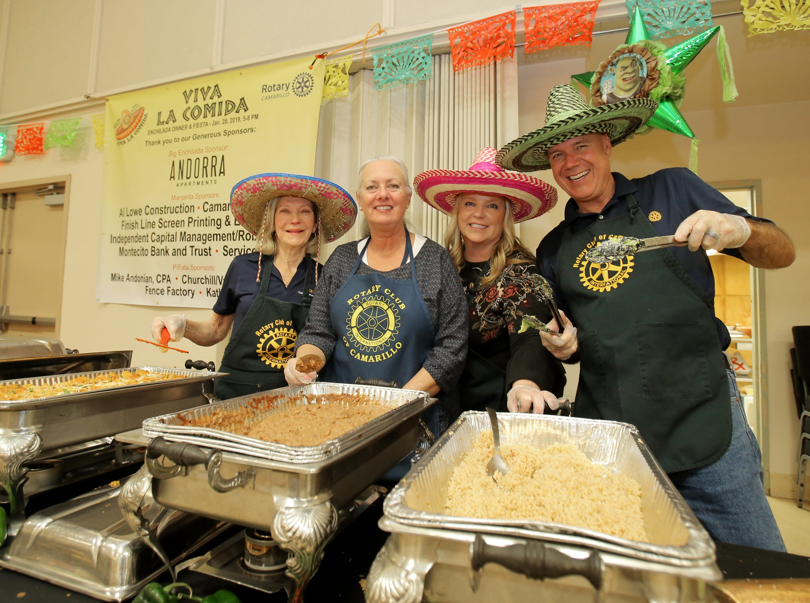 Rotary Club of Camarillo members Georgie Regnier, from left, Pat McCollum, Carrie Hughes and Dave Drumright work at one of the food stations during the Viva la Comida Dinner and Fiesta fundraiser Monday at the Camarillo Community Center. All the money raised goes toward scholarships and local charities, included the Boys & Girls Club.