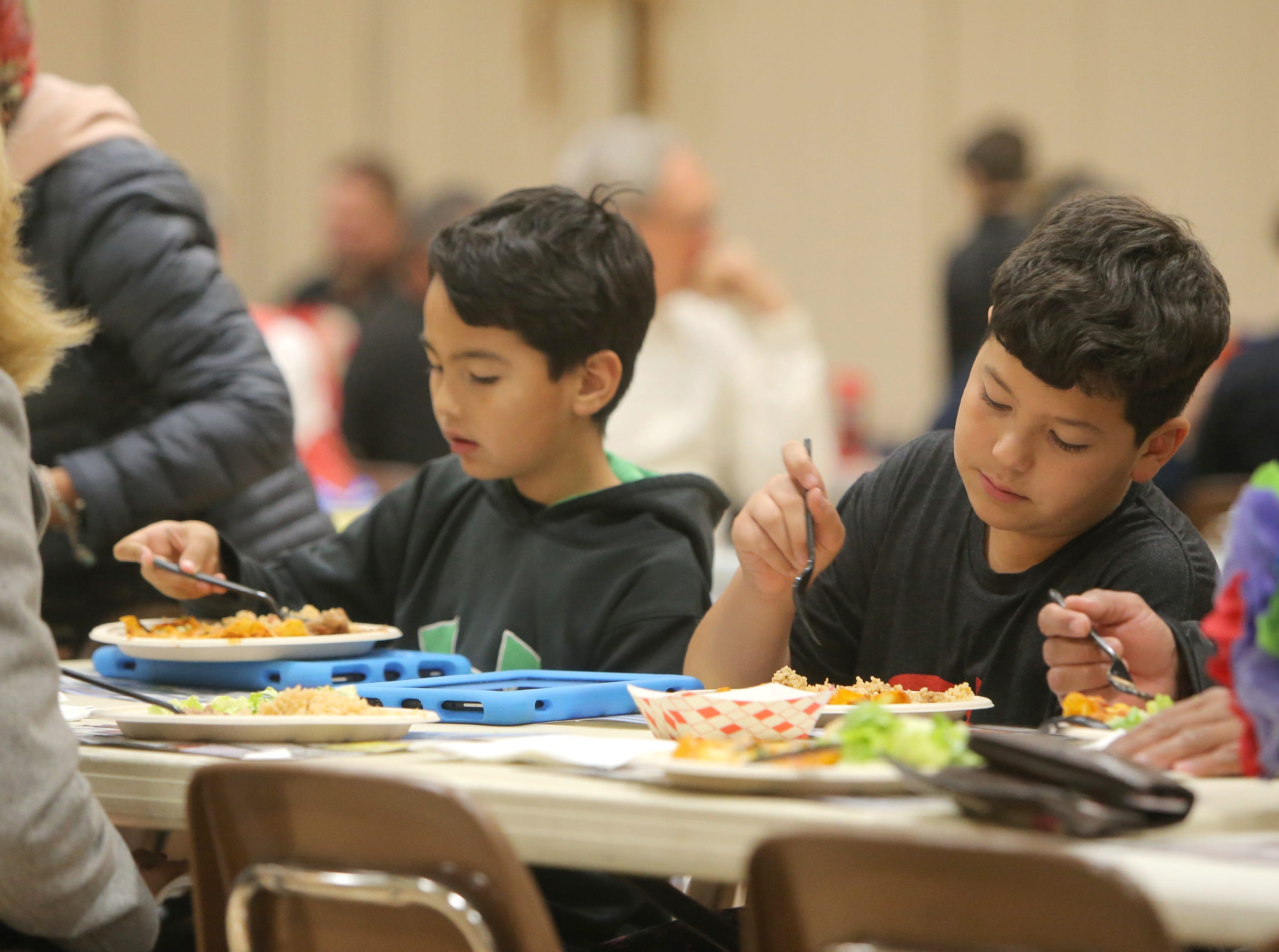 Aleck Bello, of Newbury Park, left, and his brother Aidan Bello get ready to dig into their enchiladas dinner during the Rotary Club of Camarillo's annual Viva la Comida Dinner and Fiesta fundraiser on Monday at the Camarillo Community Center.