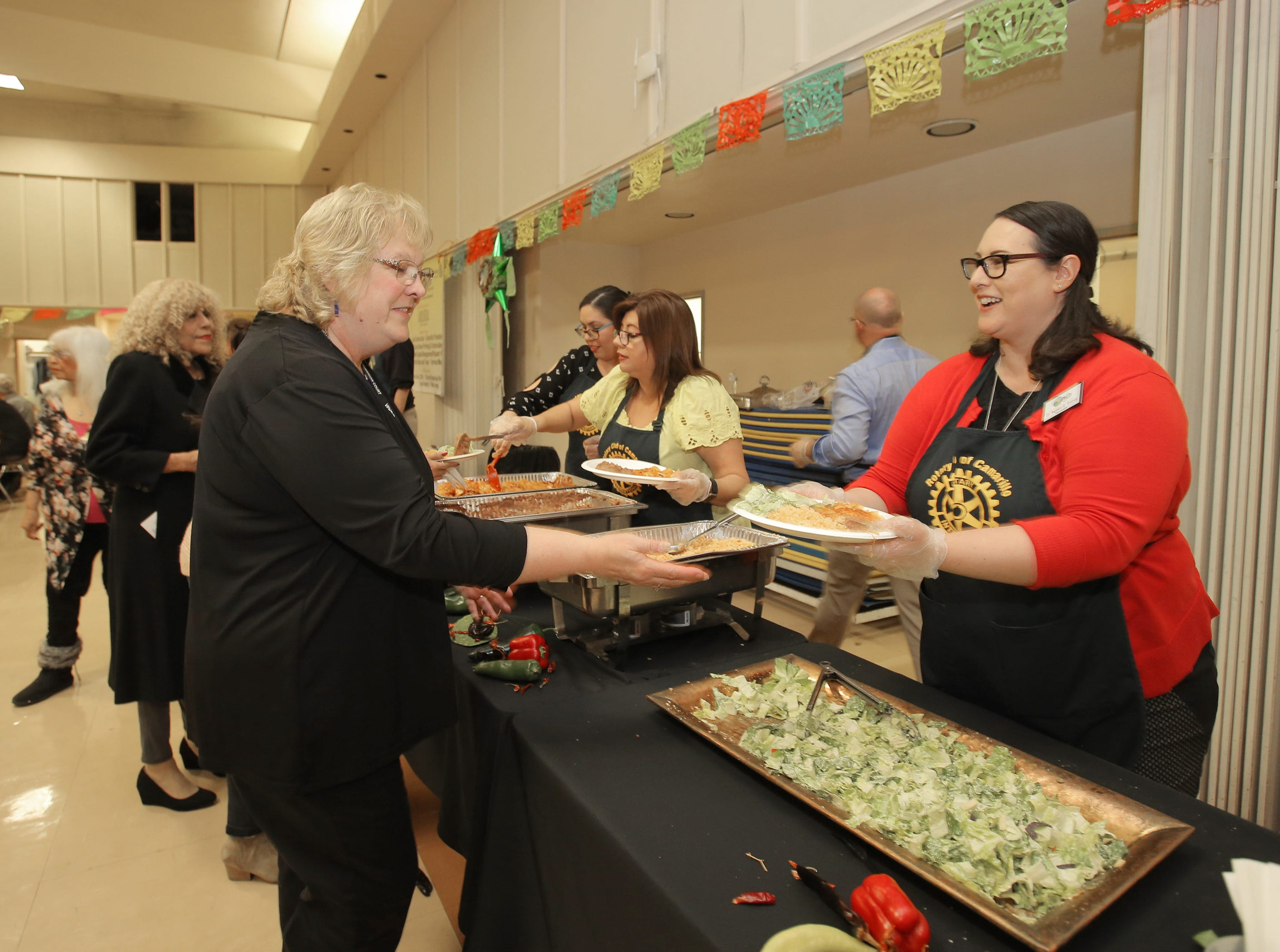 Angelica Ramsey, right, a member of the  Rotary Club of Camarillo, serves Kathleen Tillquist an enchiladas dinner during the annual Viva la Comida Dinner and Fiesta fundraiser on Monday at the Camarillo Community Center. Ramsey is the superintendent of the Pleasant Valley School District.