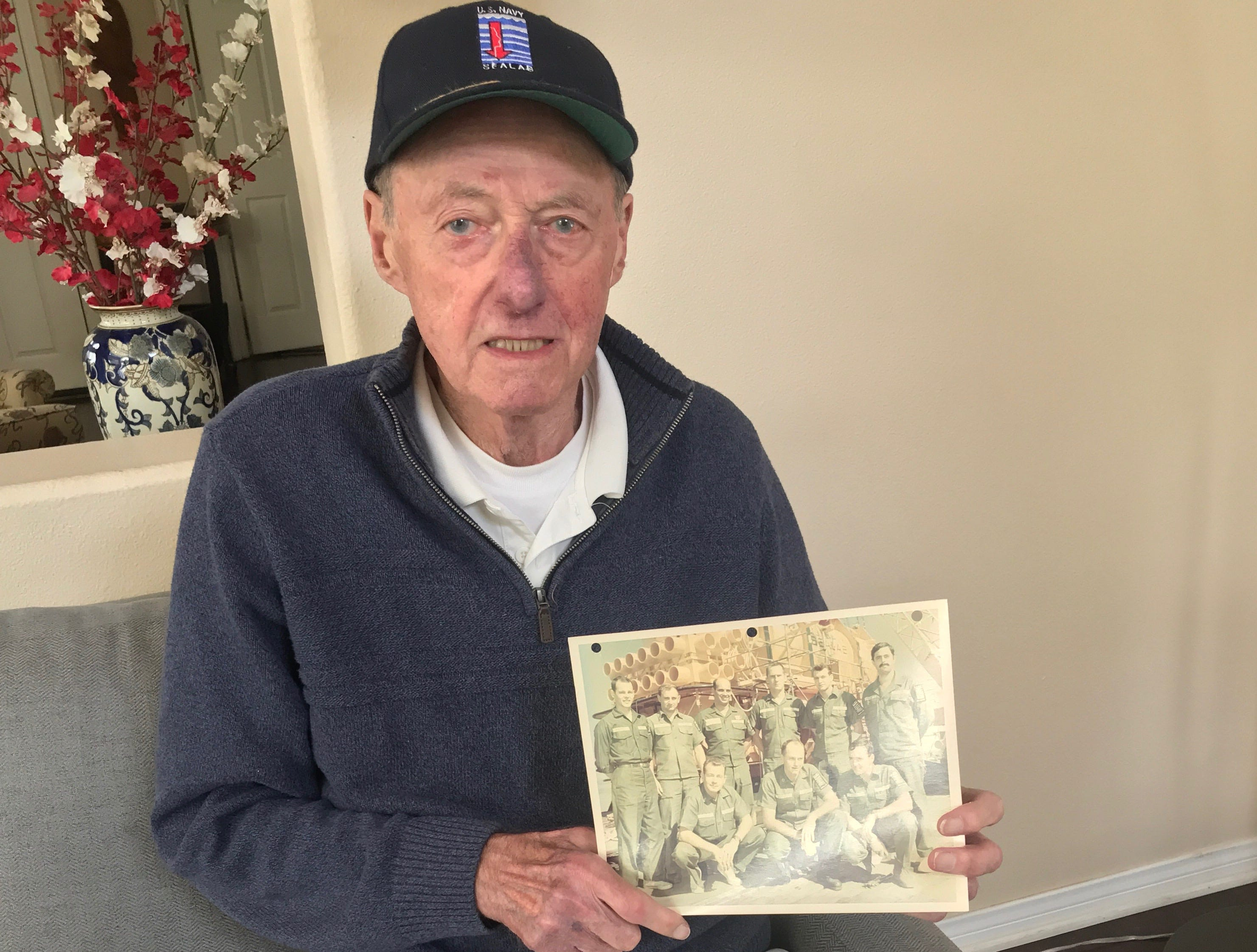 Former aquanaut Bob Bornholdt of Camarillo holds up a photo of the team he led during the 1960s-era Sealab program.