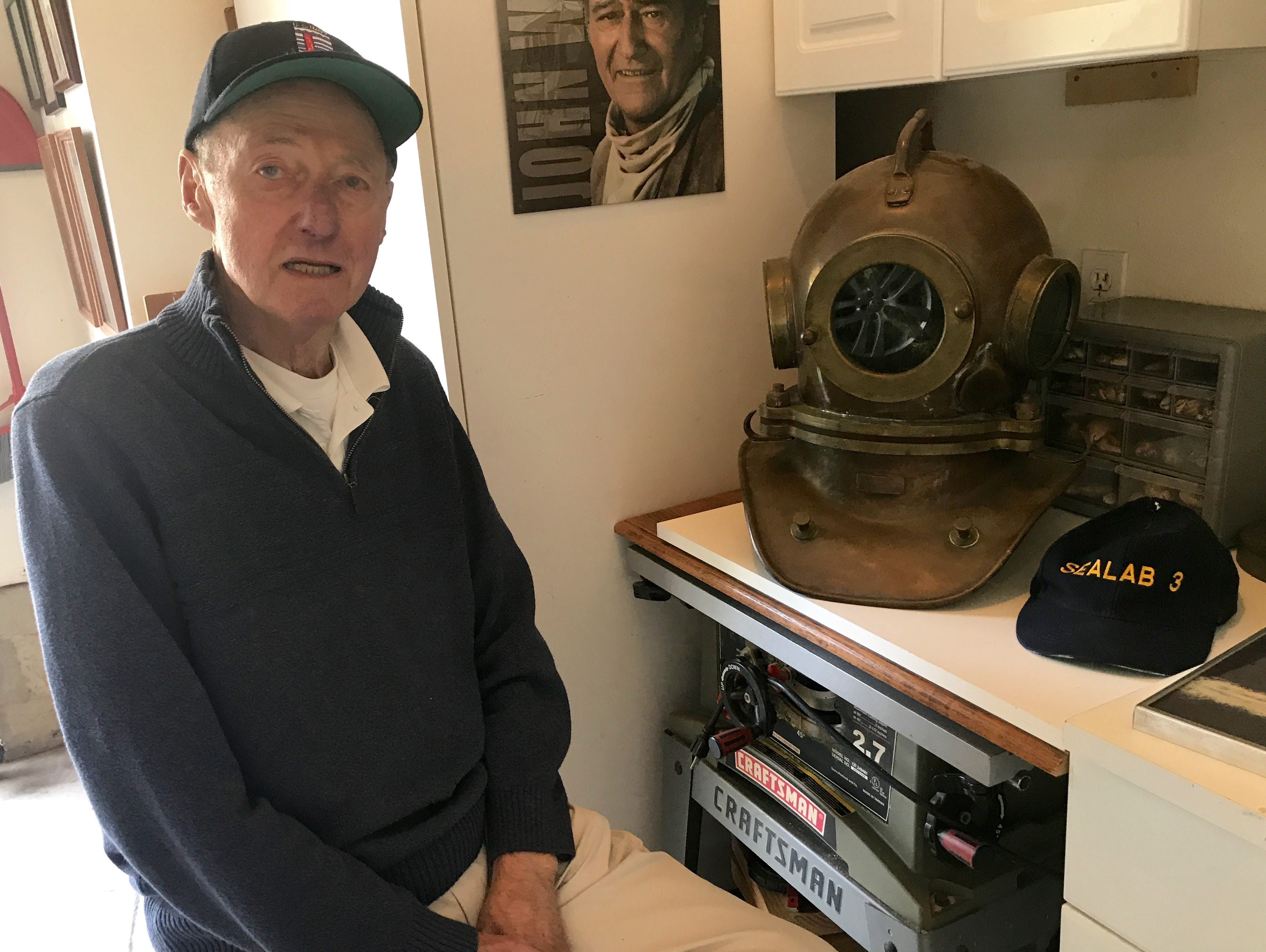 Former aquanaut Bob Bornholdt sits beside an old diving  helmet he trained in before joining the Sealab program in the 1960s.