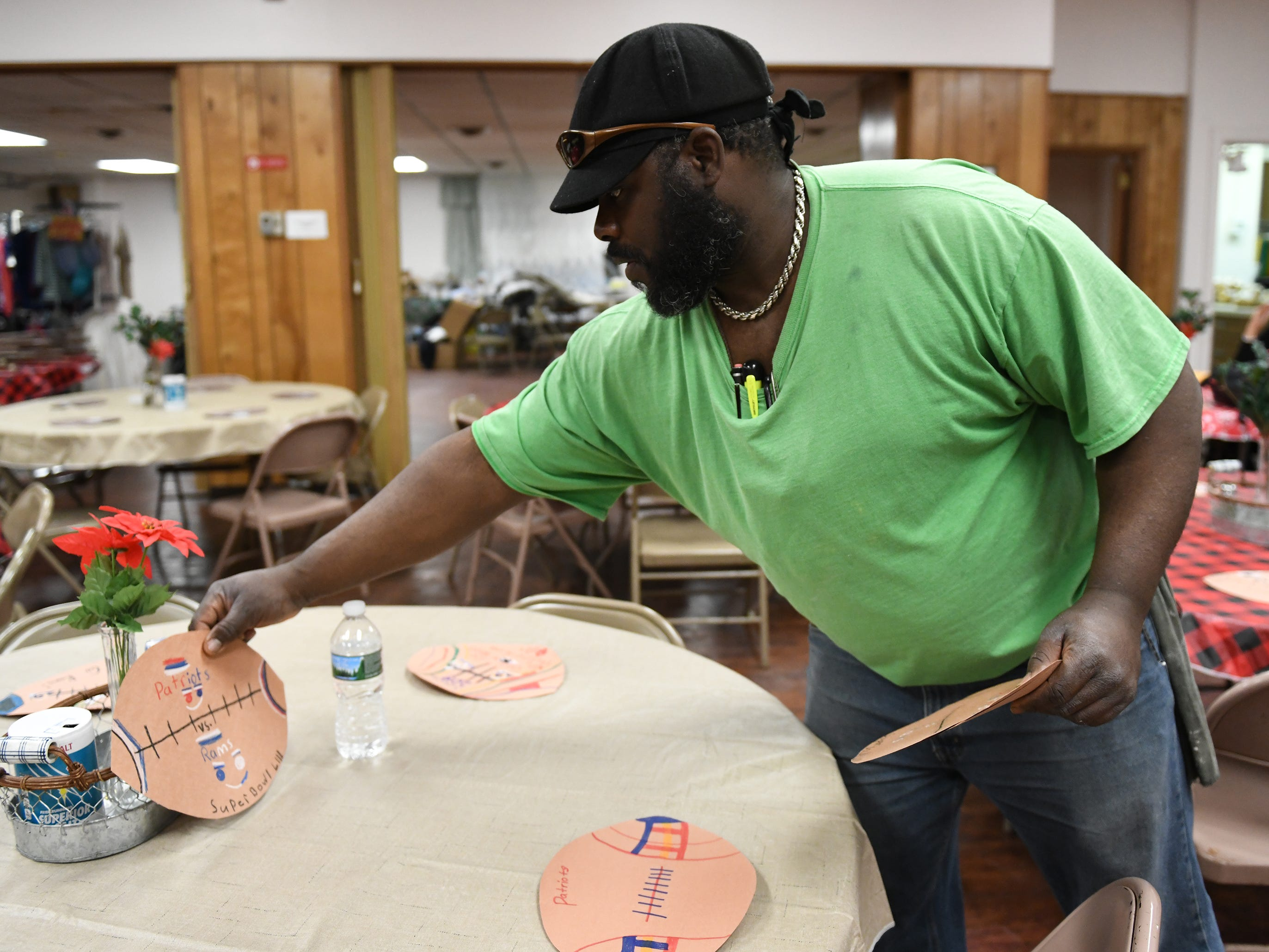 First United Methodist Church soup kitchen volunteer, Stephen W. Jones, 45, of Cumberland County, helps to set Super Bowl placemats made by Rossi Elementary School students on Tuesday, Jan. 29, 2019.