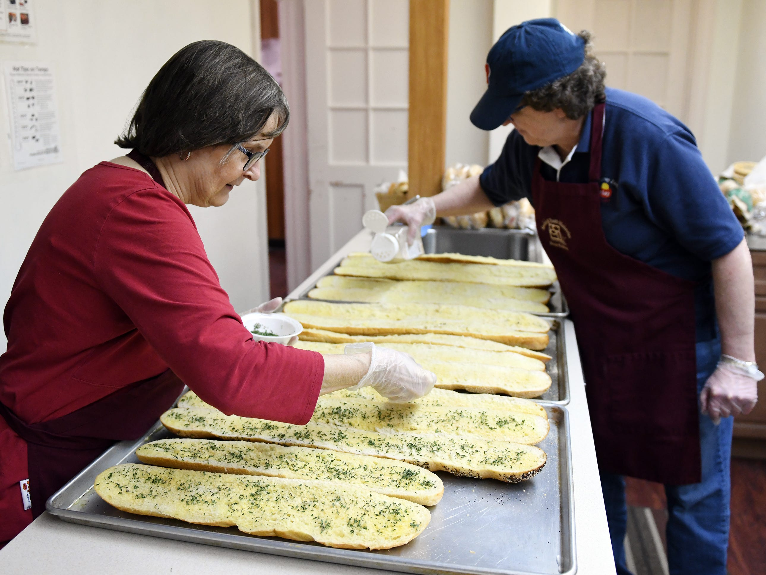 First United Methodist Church soup kitchen volunteers Barbara Cline (left) and Val Polhanus, both from Vineland, help make garlic bread in the church's kitchen on Tuesday, Jan. 29, 2019.
