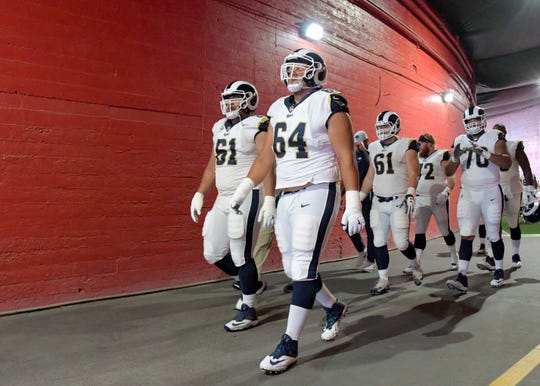 Los Angeles Rams left guard Jamil Demby (right) and Rams defensive tackle McKay Murphy (left) walk out of the tunnel before a game against the Oakland Raiders in a preseason game at Los Angeles Memorial Coliseum.