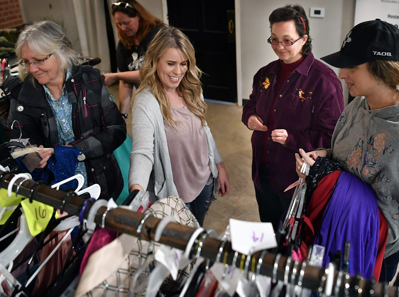 Minnetta Crowe, left, Carissa Davis and Rachel Tart, right, help Cassondra Crowe pick out a formal evening gown for Night To Shine, February 9 at OneLife Community Church.