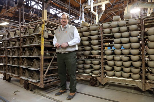 Tab Colbert, Chief Executive Officer of Ludowici Roof Tile Company in New Lexington, stands next to racks of roof tiles waiting to go in the kiln.