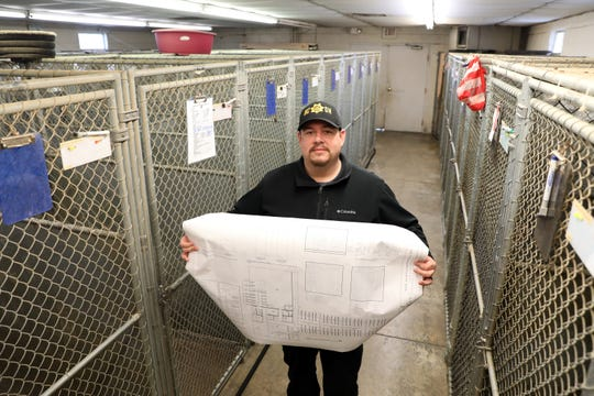 Muskingum Count Deputy Dog Warden Joshua Martinez holds plans for the new adoption center. The new facility is one of the projects expected to be undertaken by Muskingum County this year.