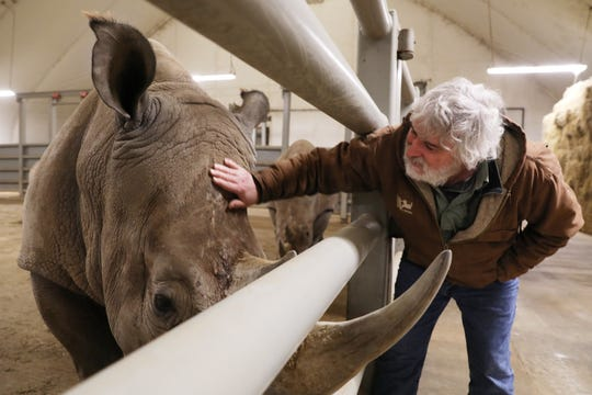 Dan Beetem, director of Animal Management at The Wilds, visits with a female and baby rhino at the conservation park.
