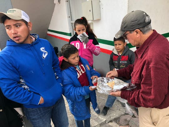 Carmen Lopez Ramirez, 25, from Tabasco, Mexico, and some of his wife's children eat tacos handed out by Mexican authorities under the International Bridge connecting Matamoros, Mexico, and Brownsville, Texas. Ramirez has been trying to cross over and seek asylum every day for several weeks. Photo by Rick Jervis, USA TODAY [Via MerlinFTP Drop]