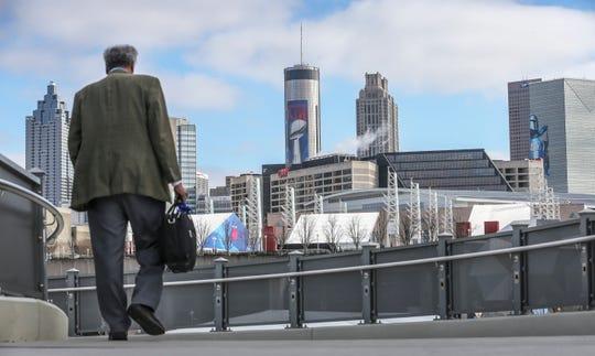 Prakash Dhamshala crosses over the Northside Drive pedestrian bridge from the Vine City MARTA station in Atlanta.