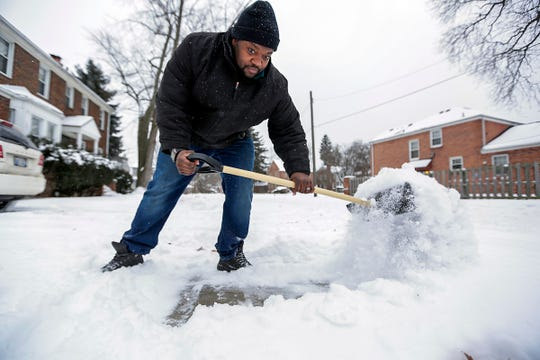 On the eve of the Polar Vortex, David Collins, 36, clears the snow from the walkways and driveway in front of his home in Detroit Jan. 29, 2019