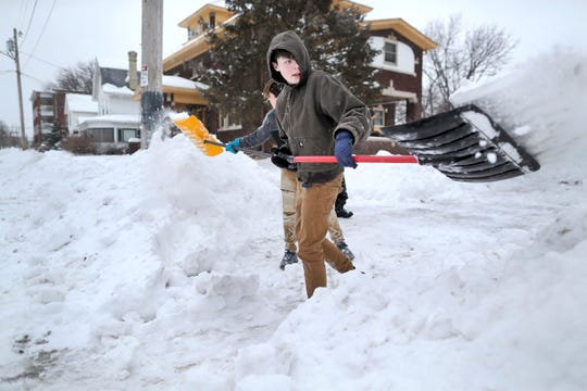 Nathan Tearman, front center, gets help from his brother James as they shovel the driveway of their home on Monday, Jan. 28, 2019, after a winter snowstorm made its way through Janesville, Wis.