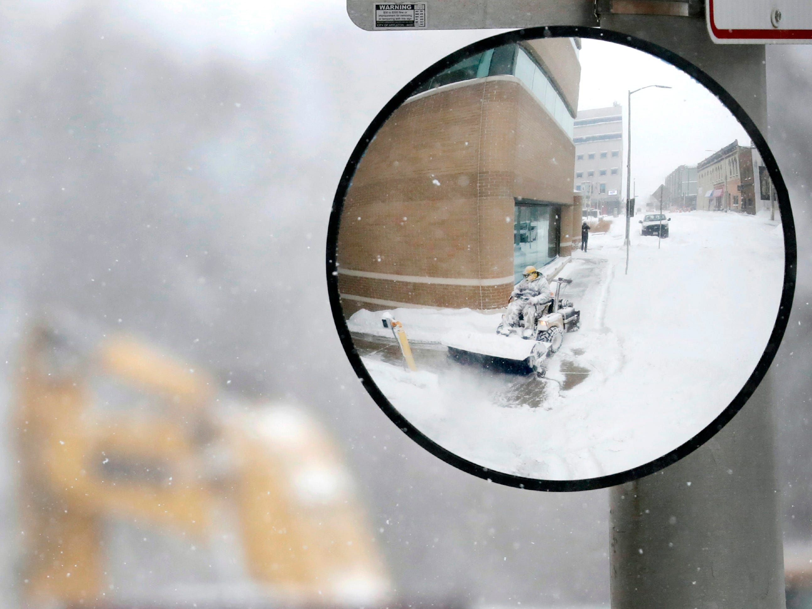 Jeff Kluever, with Pfefferle Management, is reflected in traffic safety mirror as he clears snow from a sidewalk in downtown Appleton, Wis.