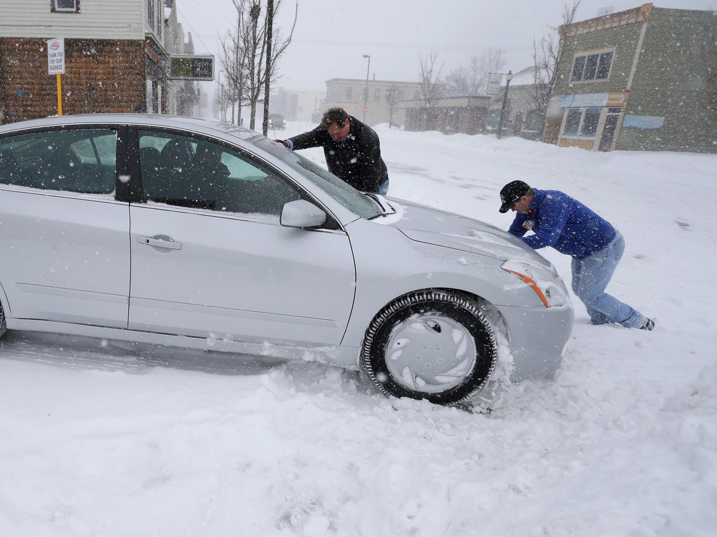 Trilling True Value's Greg Parmly, left, and Chris Schramm, help push a customer's car out of a snow bank in Sheboygan, Wis. Parmly said his store sold 15 snowblowers last week in anticipation of the storm.