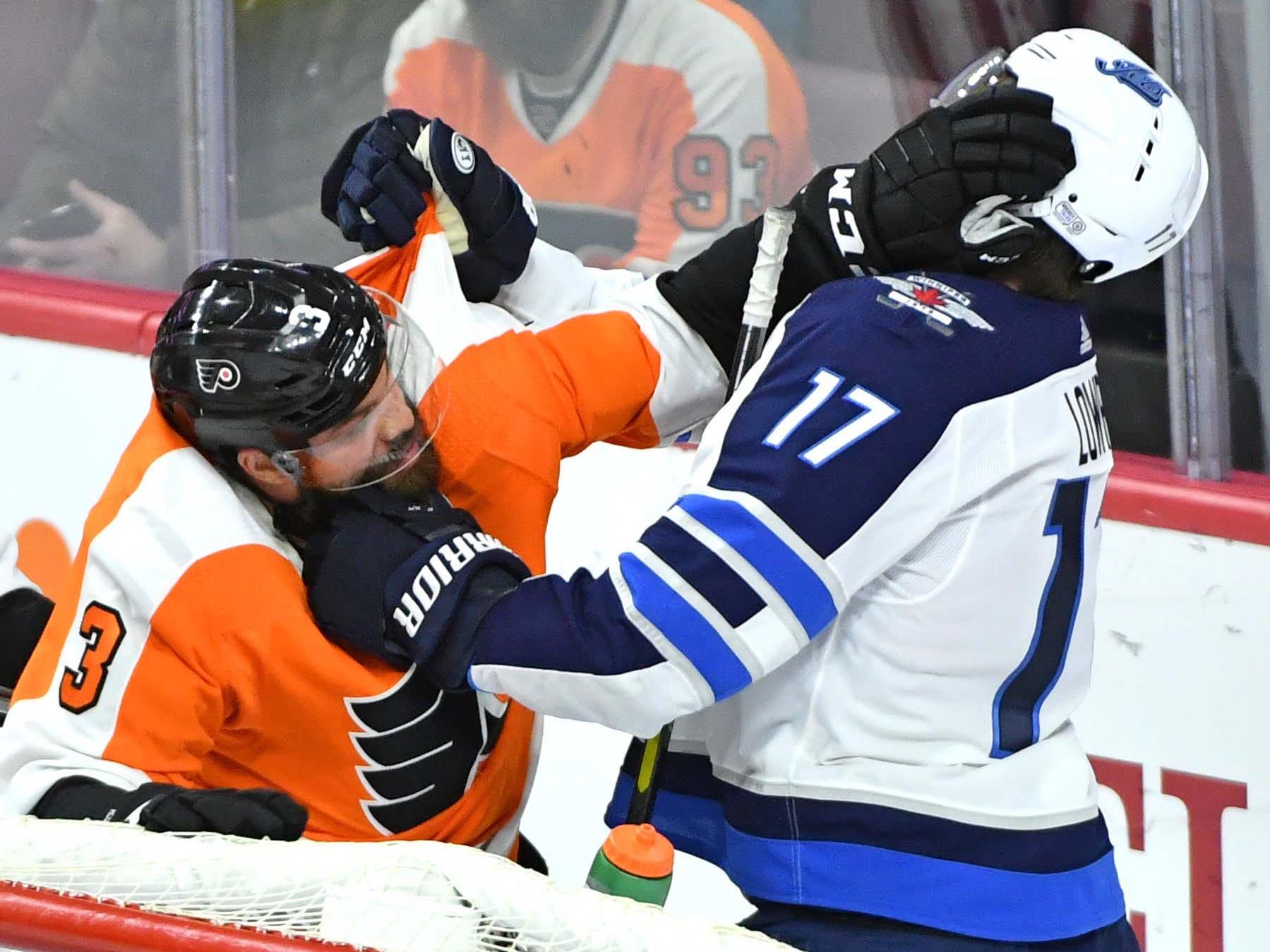 Jan. 28; Philadelphia Flyers defenseman Radko Gudas, left, battles with Winnipeg Jets center Adam Lowry during the third period at Wells Fargo Center.