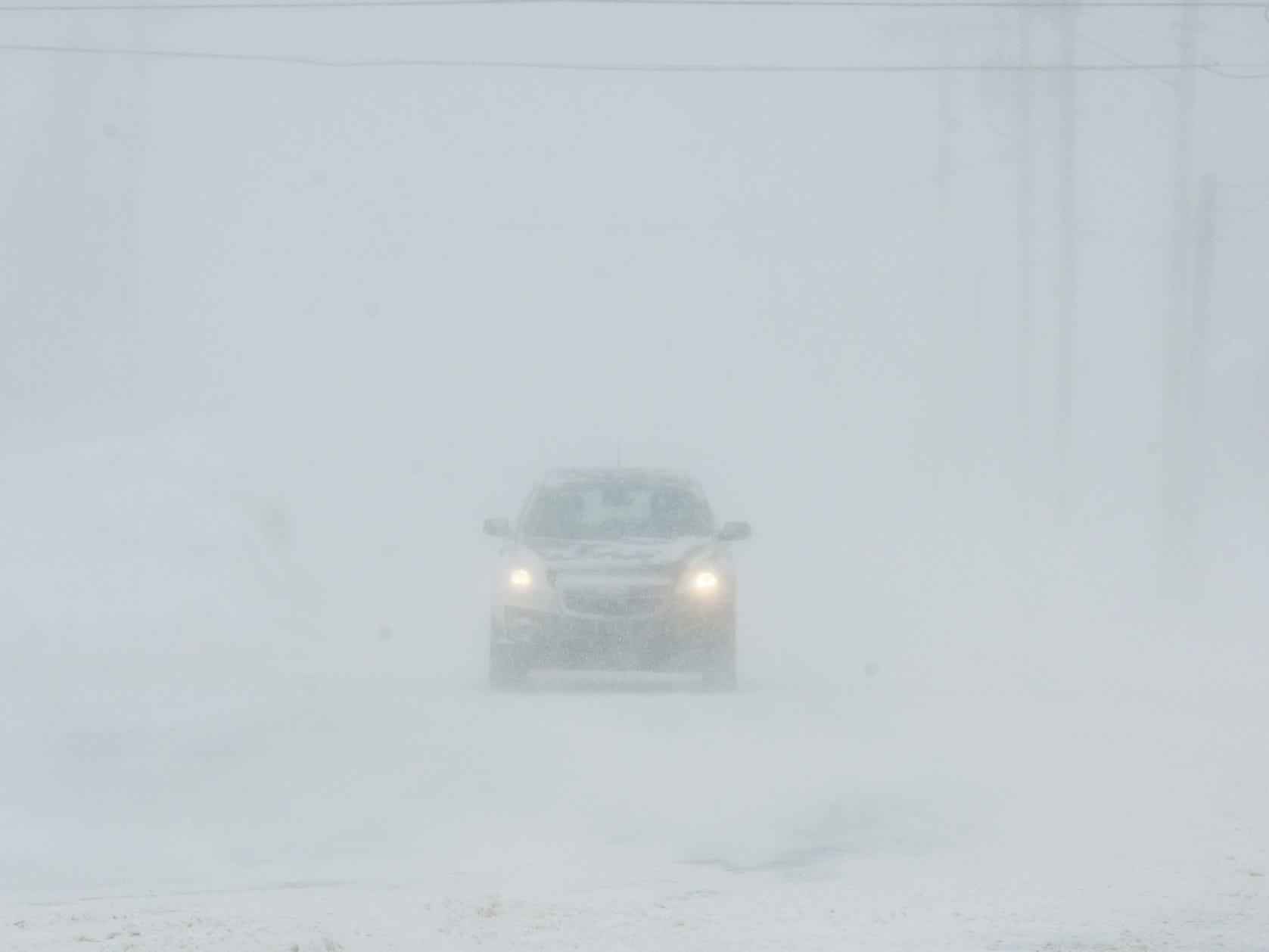 A car heads down Midway Avenue in St. Joseph, Mich., in whiteout conditions, Jan. 29, 2019, after a winter storm dumped several inches of snow in Southwest Michigan.